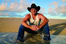 Man in black hat sitting on ground