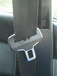 Hebilla de cinturón de seguridad de tres puntos colgando del pilar B de un automóvil.