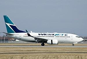 English: Westjet 737-700 landing at Montréal-P...