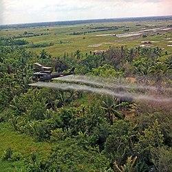 Um helicóptero UH-1D espalhando agente laranja em uma floresta na região do delta do Mekong (1969)