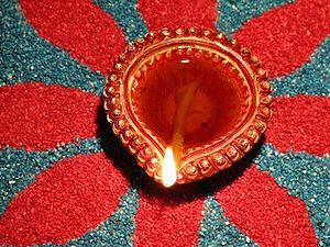 Burning oil lamp on a colourful rangoli design...