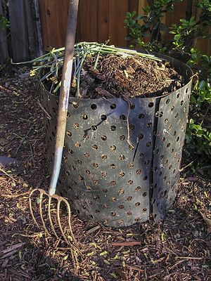 A pitchfork next to a compost bin.