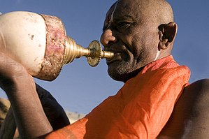 A Hindu priest blowing his conch during a puja...