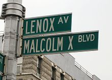 Two green street signs, one reading Lenox Avenue, the other reading Malcolm X Boulevard