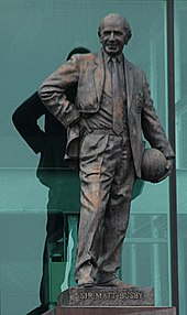 A statute of Sir Matt Busby holding a ball