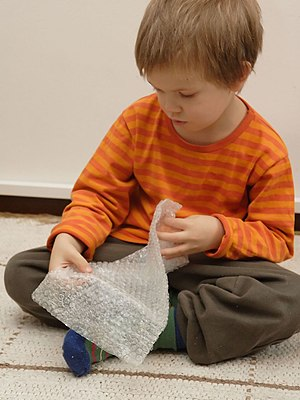 Boy playing with bubble wrap