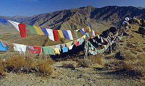 Lungta-style prayer flags hang along a mountai...