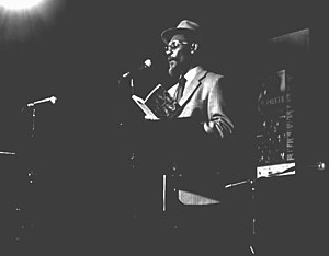 Linton Kwesi Johnson on stage reading from a book