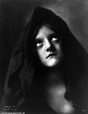 English: Young woman with head draped looking ...