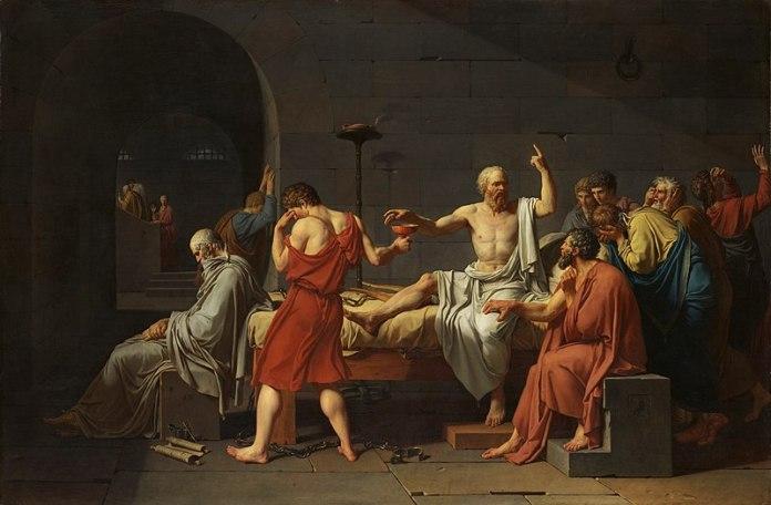 Socrate au centre, dirige sa main vers une coupe que lui tend un homme, autour de lui, ses disciples