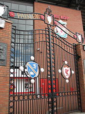 """A set of gates with the inscription """"Paisley Gateway"""" at the top. In the middle of the sets of gates are two emblems"""