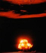 A fiery mushroom cloud lights up the sky.