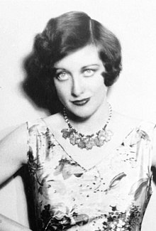 Upper body studio shot of a young Crawford in a sleeveless dress, with accented eye make-up, coiffed hair. She is staring into the c am era.