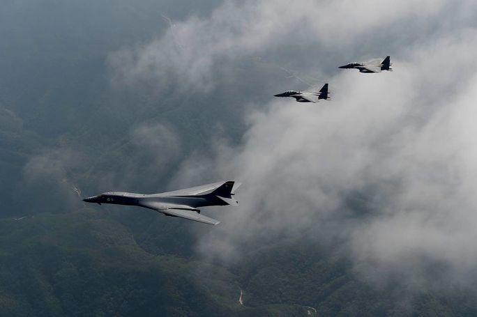 A U.S. Air Force B-1B Lancer is flanked by two F-15K Slam Eagles (29942752785)