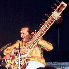 A man sits cross-legged and holds a long-necked lute while looking to the side.