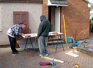 A carpenter and his mate prepare a door for in...