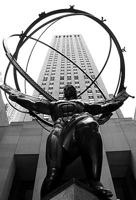 A statue of a muscular man holding a hollow globe on his shoulders. A skyscraper towers above the statue in the background.