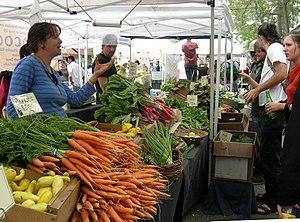 Seorang penjual sayur di sebuah pasar.
