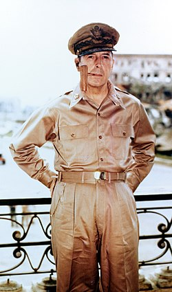 MacArthur in khaki trousers and open necked shirt with five-star-rank badges on the collar. He is wearing his field marshal's cap and smoking a corncob pipe.