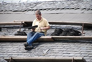 A slater working on the roof of a house in Bis...