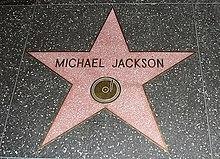 "Sebuah bintang merah muda dengan bibir warna  emas dan tulisan ""Michael Jackson"" di tengah bintang. Bintang  menjorok ke dalam tanah dan dikelilingi oleh warna lantai marmer."