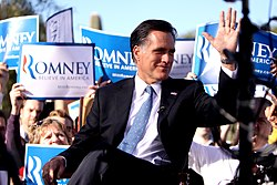 """Mitt Romney sitting outdoors during daytime, with crowd behind him holding up blue and white """"Romney"""" signs"""