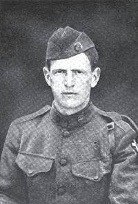 Head and shoulders of a stern faced man in a military uniform with breast pockets, shoulder straps, and garrison cap.