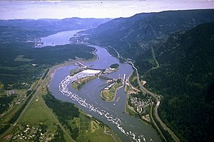 Aerial view of a large river winding through a mountainous gorge. It passes over a dam stretching in four segments from bank to bank across three intervening islands. Highways, passing by clusters of buildings here and there on both banks, run parallel to the river. Whitewater and foam curl downriver from one of the central segments.
