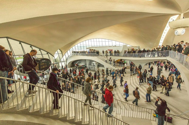 A wide-angle photograph of visitors at the TWA Flight Center at JFK airport