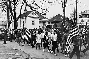 Participants, some carrying American flags, ma...