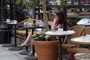 English: A young woman in a cafe, talking in a...
