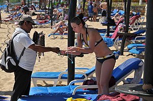 A woman wearing a bikini inspects a salesman's...