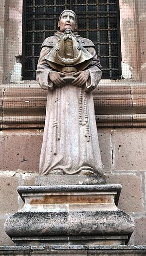 English: Statue of a Franciscan monk with an i...