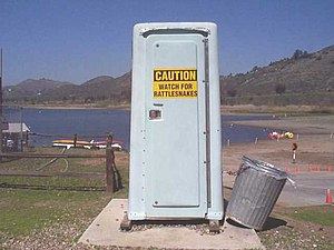 Porta-potty with rattlesnake warning sign at L...
