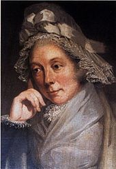 Quarter-length portrait of a woman in a brown and gray lace bonnet adorned with a bow and leaning on her right hand.