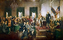 A crowd of men gathered in a hall with chandeliers and American flags.