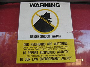 A neighborhood watch sign attached to a door.