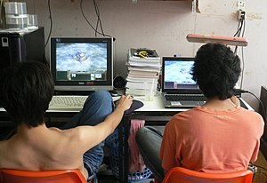 Two men are using their computers (playing com...