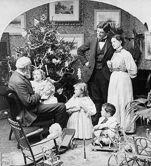 Family with toys in front of Christmas tree.