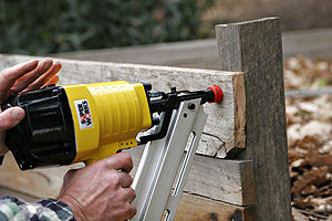 Pneumatic nail gun in use