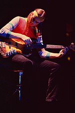 A color photograph of Jaco Pastorius sitting on a stool and playing a bass guitar