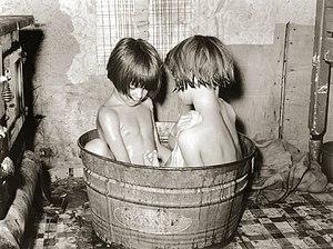 English: Kids bathing in a small metal tub. Th...