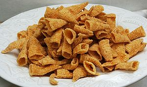 Snack food made from corn formed into hollow, ...