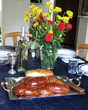 Table set for Shabbat with challah and wine.