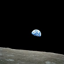 The small blue-white semicircle of the Earth, almost glowing with colour in the blackness of space, rising over the limb of the desolate, cratered surface of the Moon.