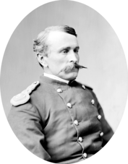 Head and torso portrait of a white man with a pointed mustache wearing a military jacket.