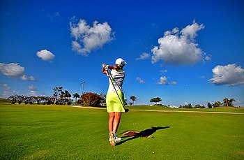 English: A female golfer takes a shot at a golf course in Cayman Islands