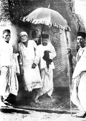 Shirdi Sai Baba, leaning against the wall of h...