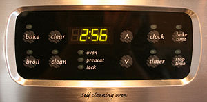 A digital clock built into an oven.