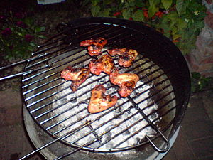 Chicken wings being cooked slowly over charcoa...